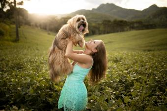 Woman with her dog lhasa apso in nature