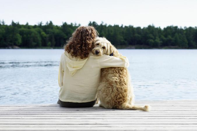 Woman sitting with dog on dock