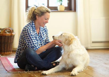 Woman petting her dog at home