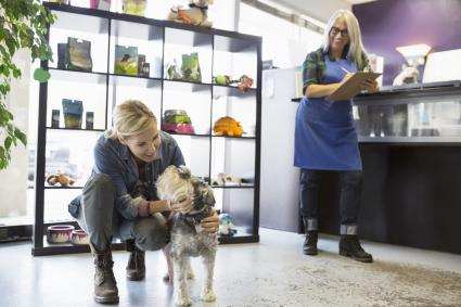 Woman saying goodbye to schnauzer at dog daycare