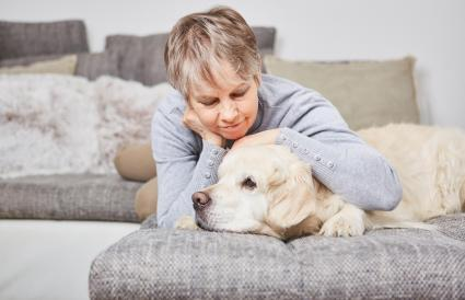 Senior Woman With Dog On Sofa At Home
