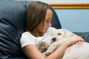 Little girl cuddling her sick dog