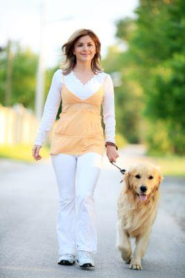 Image of a woman walking her Golden Retriever