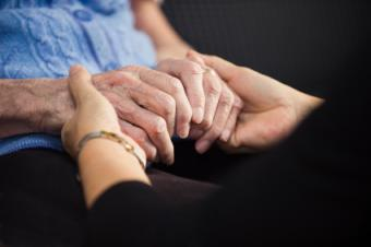 Home hospice worker holding a patient's hands