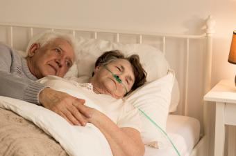 Senior man holding terminally ill wife