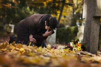 man visiting grave at cemetery