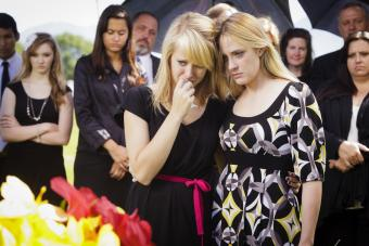 Two teenagers standing beside a casket at a funeral