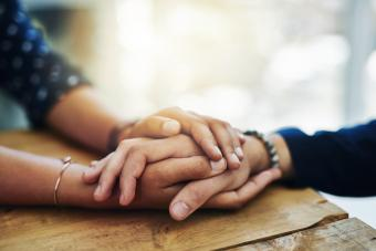 People holding hands in comfort