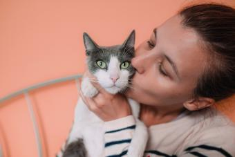 Woman kissing grey and white cat