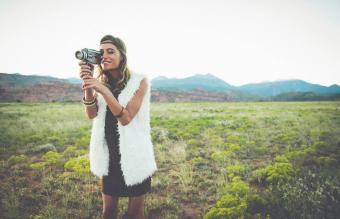 woman filming in rural field