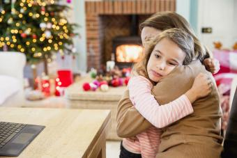 Sad little girl is cuddling with her mother at christmas time