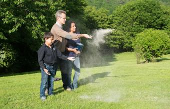 Family scattering ashes in a garden