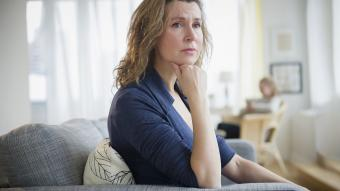 Concerned woman sitting on sofa