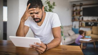 Worried father on tablet at home