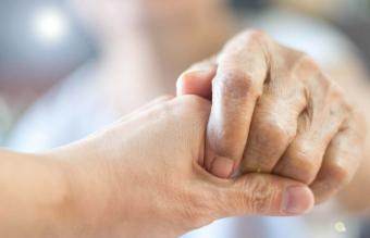 holding elder hand woman in hospice care