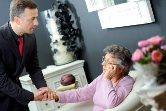 Funeral director holding hand of elderly lady