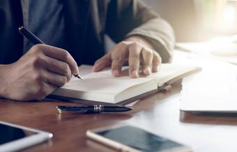 man writing in book on table