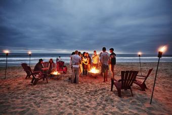 Friends gathered around fire on beach