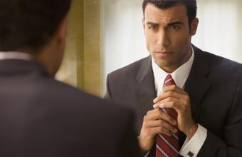 Man in business suit adjusting tie in mirror