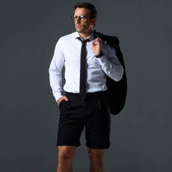 man in shorts holding jacket on shoulder