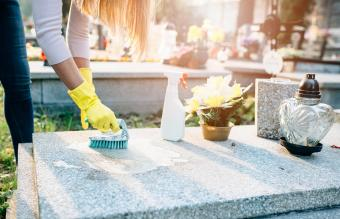 Washing tombstone with brush