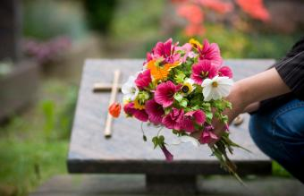 Woman leaving flowers at grave