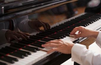 hands playing on a piano at funeral