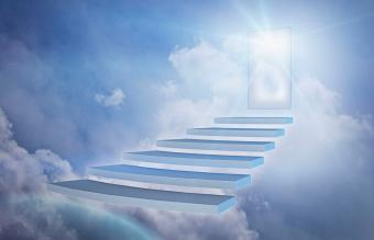 Staircase in clouds with glowing doorway