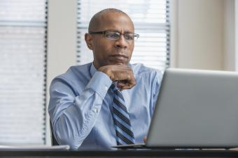Man with pensive look working on laptop