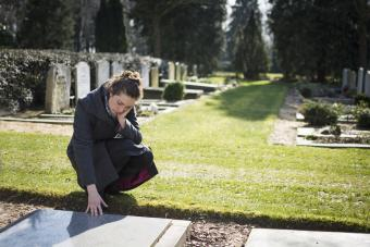 Sad woman lovingly touching gravemarker