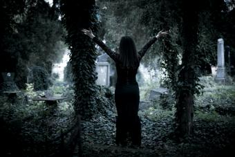 Young woman standing in an overgrown cemetery with hands stretched out