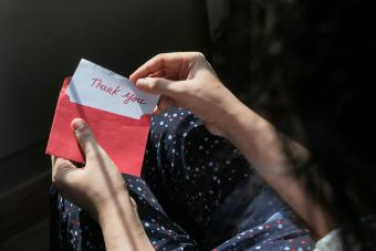 woman holding thank you note