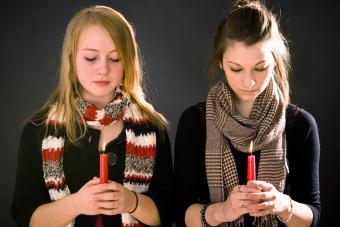 Two young women look down at burning candles and remember during a moment of silence