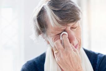 Weeping old woman wipes her eyes