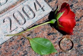 GgGold wedding band and fresh red rose bloom lay atop a marble grave marker