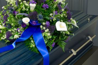 A blue coffin with a flower arrangement