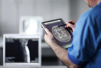 Doctor holding portable computer with MR scan