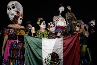 Participants seen dressed as the dead while holding a Mexico flag during the parade