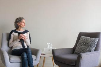 Middle aged woman seated looking pensive in living room with second empty armchair