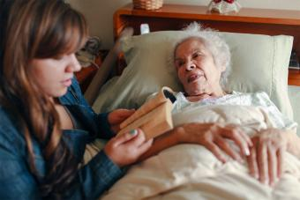 granddaughter reading to dying grandmother