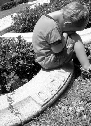 Little boy at his father's grave