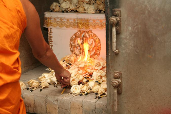 Buddhist monk putting lights on coffin