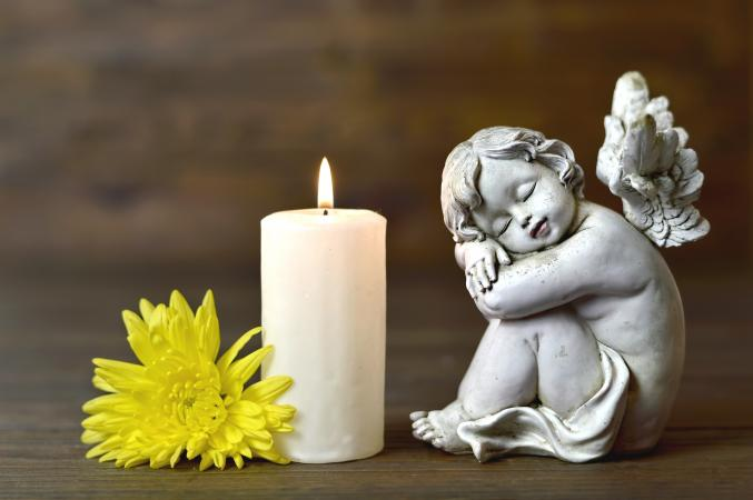Image of cherub statue, candle and yellow mum