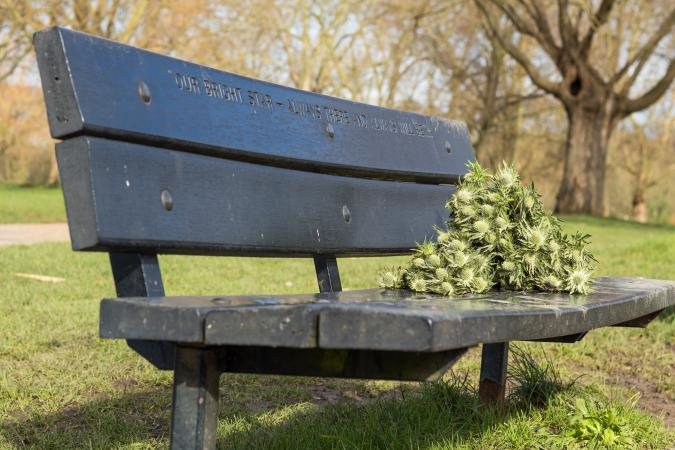 Wooden memorial bench with old flower bouquets