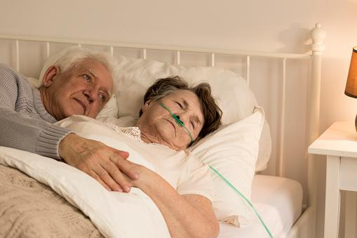 Senior man holding terminally ill wife