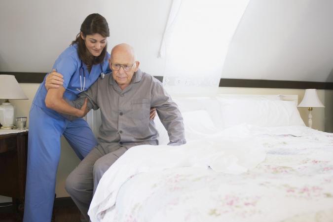 Hospice nurse helping elderly man