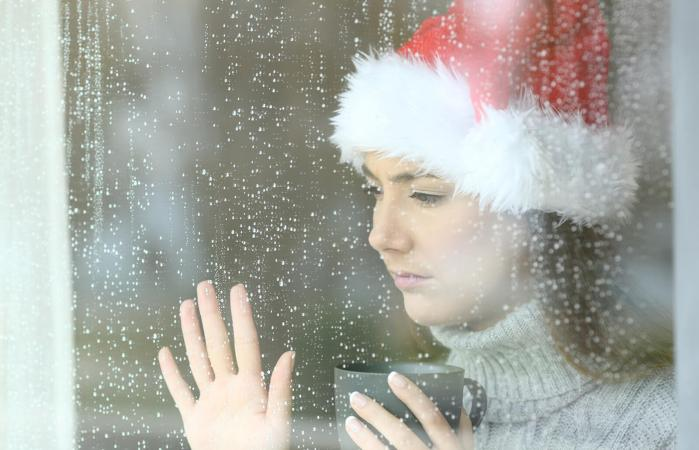 Woman wearing santa hat looking longingly out the window