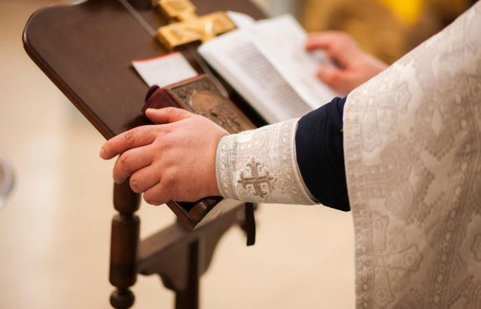 Hands of priest on pulpit
