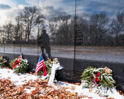 Vietnam Memorial with flags and wreaths and remaining snow