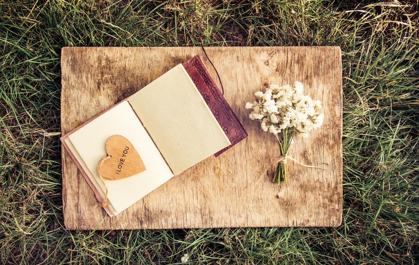 An open book with empty pages, a bouquet of white flowers and a wooden heart